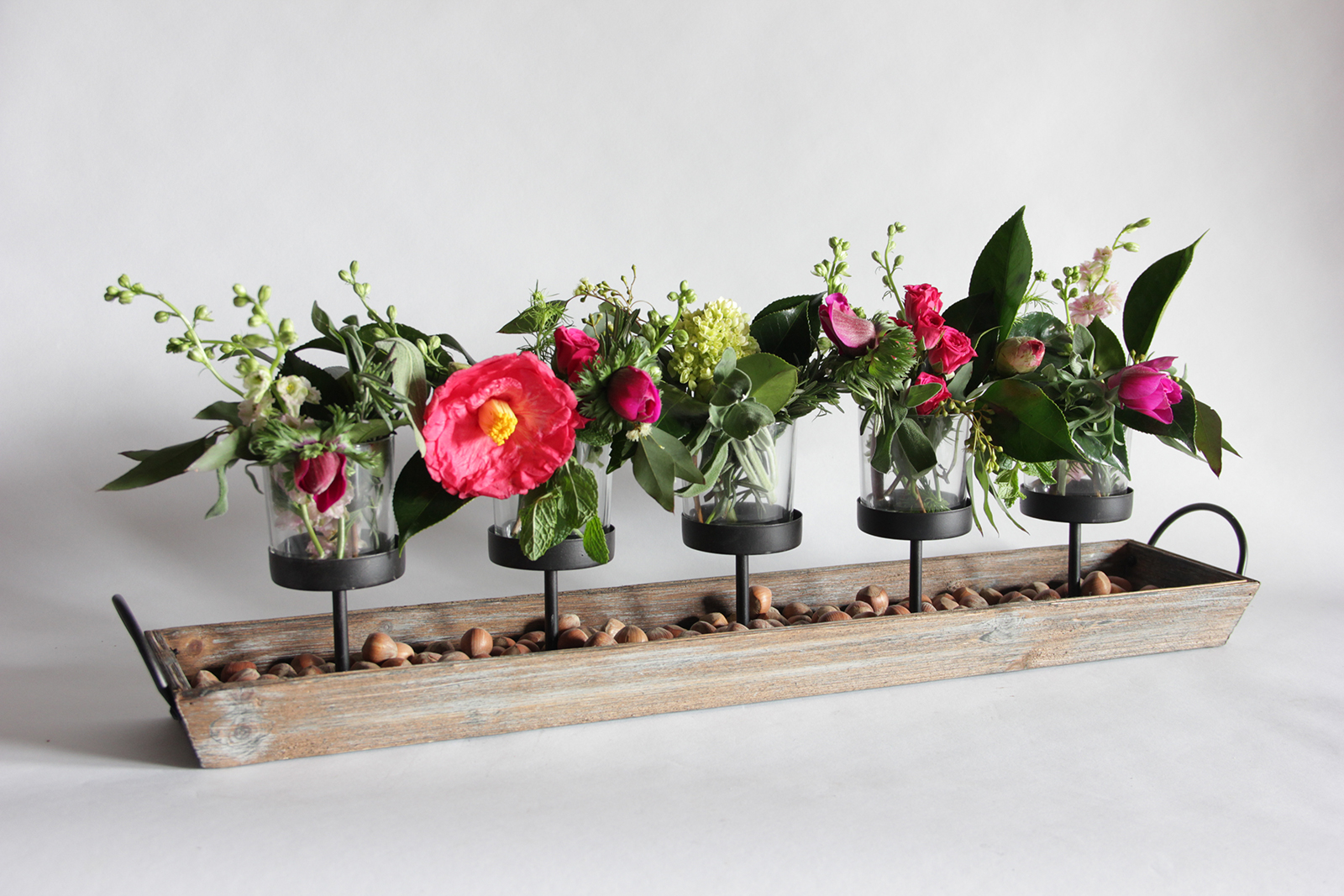 votive holder with mini flower bouquets and hazelnuts